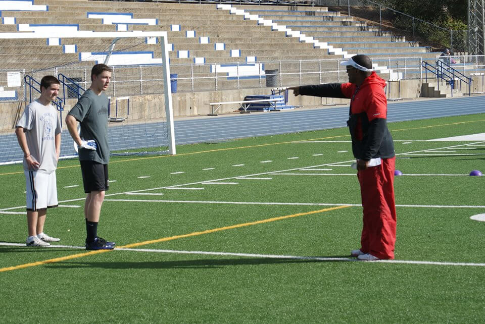 Thomas coaching an aspiring football player